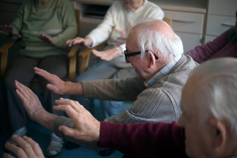 Bewohnerinnen und Bewohner einer ambulant betreuten Wohngemeinschaft beim Training zur Verbesserung ihrer motorischen und kognitiven Fähigkeiten